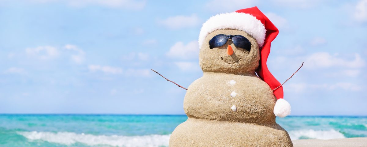 Snowman in red santa hat on beach/holiday concierge services/starting a concierge business/Build a Personal Concierge Business/How to grow a Concierge Business/www.theconcieregeacademy.com
